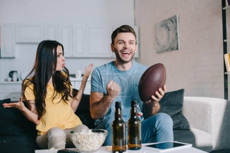angry young woman yelling at husband while he watching american football on tv at home