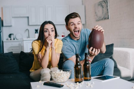 Photo for Expressive young couple cheering for american football game at home - Royalty Free Image
