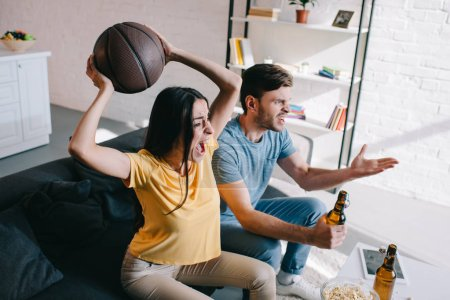 high angle view of emotional young couple with beer cheering for basketball game at home