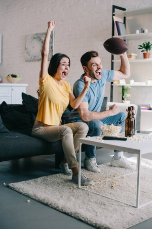 emotional young couple cheering for american football game at home