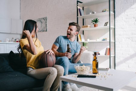 emotional young couple with beer cheering for basketball game at home