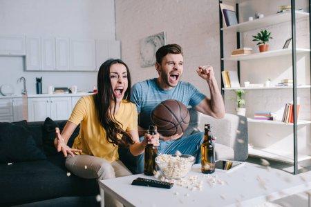 expressive jeune couple avec bière réjouissant pour le match de basket à la maison