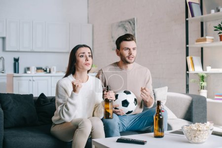 Photo for Excited young couple watching football game on couch at home - Royalty Free Image