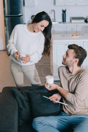Foto de Sonriente pareja joven con tazas de cacao y relajarse juntos en casa de la tableta - Imagen libre de derechos