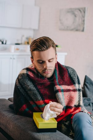 sick young man taking paper napkins from box while sitting on couch