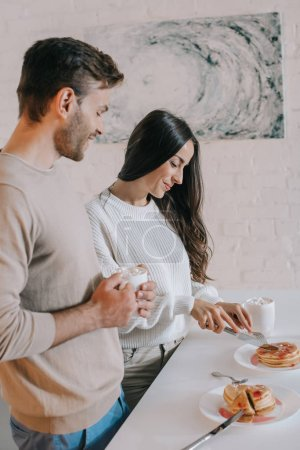 beautiful young couple with pancakes for breakfast at home