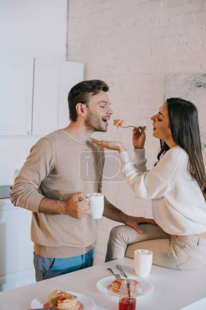happy young woman feeding her boyfriend with pancakes for breakfast