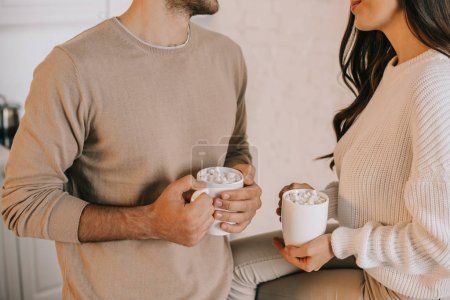 cropped shot of young couple holding mugs of cocoa with marshmallow