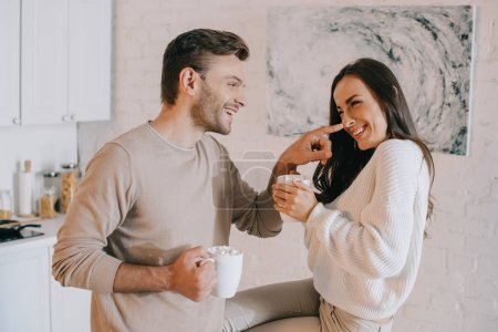 happy young couple with cocoa and pancakes cuddling on kitchen