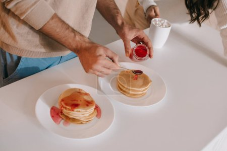 cropped shot of couple pouring jam onto pancakes for breakfast