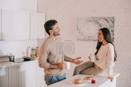 beautiful young couple having breakfast together and chatting at home