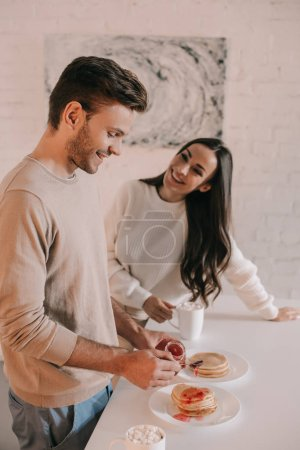 beautiful young couple with pancakes with jam for breakfast at home
