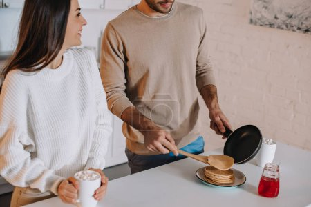 cropped shot of young couple making pancakes for breakfast together at home