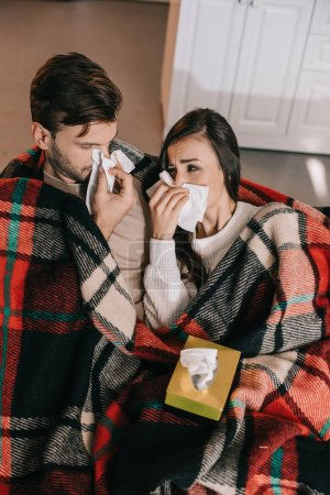 ill young couple with paper napkins sneezing while sitting on couch under plaid at home