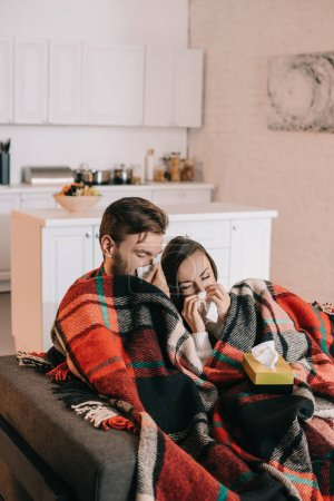 diseased young couple with paper napkins sneezing while sitting on couch under plaid at home