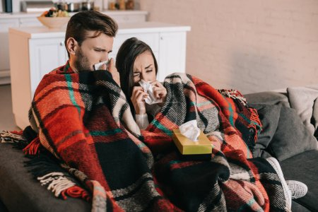 Photo for Sick young couple with paper napkins sneezing while sitting on couch under plaid at home - Royalty Free Image