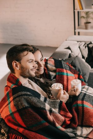 smiling young couple with cups of cocoa with marshmallow relaxing on couch under plaid at home
