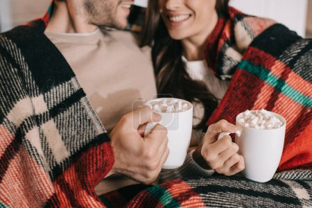 Photo for Cropped shot of smiling young couple with cups of cocoa with marshmallow relaxing on couch under plaid at home - Royalty Free Image