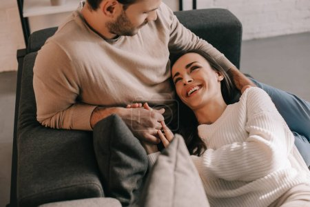 Photo for Happy young couple relaxing on couch together at home - Royalty Free Image