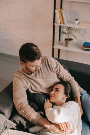Photo for High angle view of beautiful young couple relaxing together on couch at home - Royalty Free Image