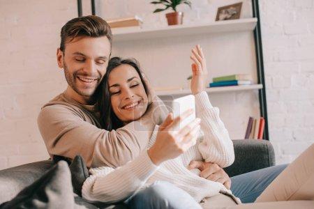 Photo pour Jeune couple souriant utilisant un smartphone ensemble sur le canapé à la maison - image libre de droit