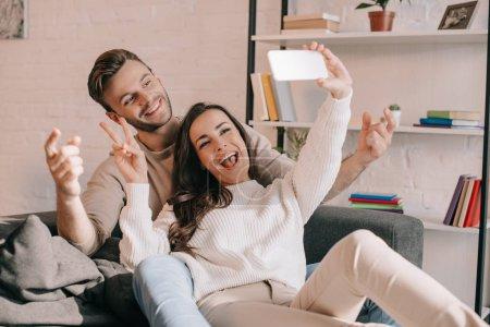 Photo pour Heureux jeune couple prenant selfie avec smartphone et faisant le geste de paix sur canapé à la maison - image libre de droit