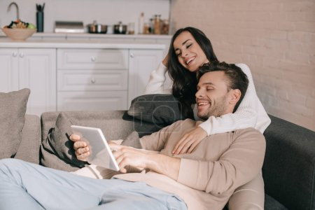 Photo for Laughing young couple using tablet together on couch at home - Royalty Free Image