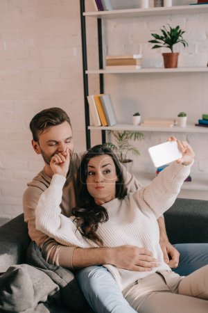 playful young couple taking selfie with smartphone on couch at home