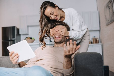 beautiful young woman covering eyes of boyfriend while he using tablet at home