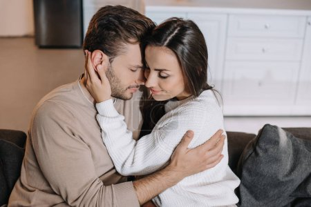 beautiful young couple embracing on couch at home