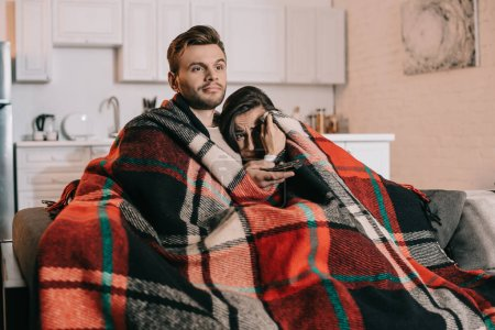 young couple relaxing on couch and watching tv together while covering with plaid