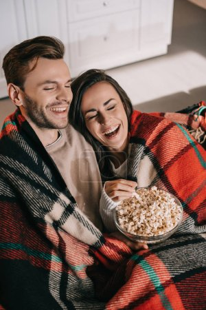 high angle view of happy young couple watching movie with popcorn on couch and covering with plaid