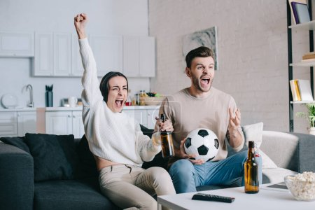expressive young couple watching football game at home and cheering