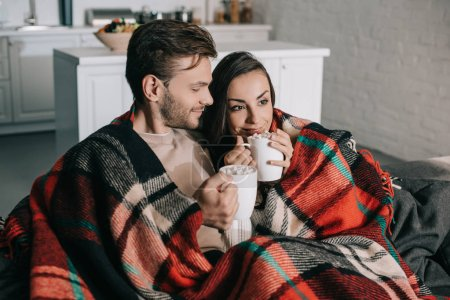 Photo for Happy young couple with mugs of cocoa with marshmallow relaxing on couch and covering with plaid - Royalty Free Image