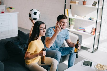 expressive mad young couple watching football game at home
