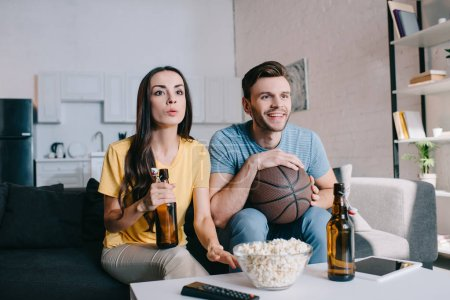 happy young couple watching basketball game on tv at home