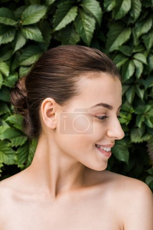 smiling young woman with green leaves at background