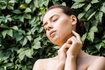 junge Frau mit händennahem Gesicht auf grünem Laubhintergrund
