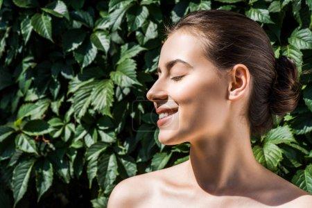 jeune femme avec des yeux fermés et beau sourire contre feuilles vertes à fond