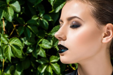 young beautiful woman with glittery makeup and closed eyes at green leaves background