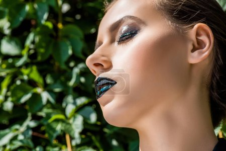 Photo pour Jeune femme avec des lèvres noires et feuilles vertes à fond - image libre de droit