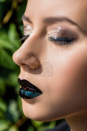 close up of young woman with closed eyes at green background