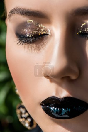 close up of beautiful young woman with closed eyes and green background