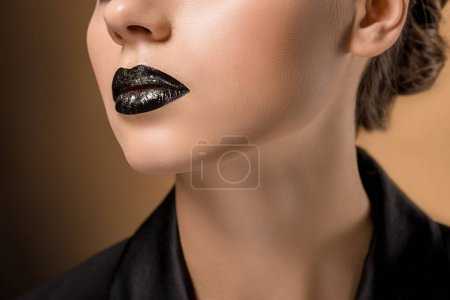 close up of young beautiful woman with glittery black lips