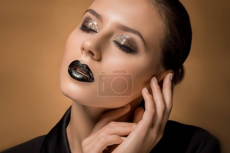 young beautiful woman with glittery makeup and hands near face
