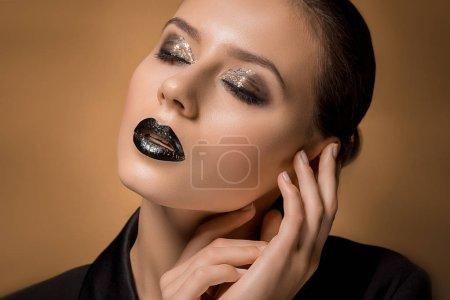 belle jeune femme avec les mains près de visage et de maquillage pailleté