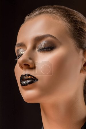 young beautiful woman with glittery makeup and closed eyes