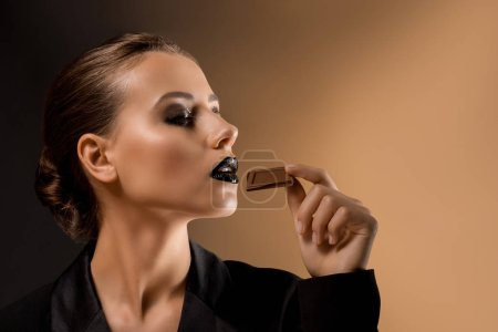 young beautiful woman with glittery makeup eating chocolate