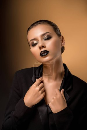 young beautiful woman with glittery makeup holding black jacket