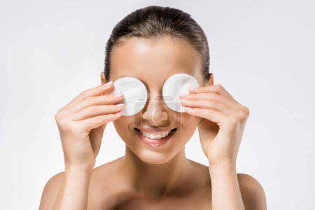 young smiling woman holding cotton pads on eyes
